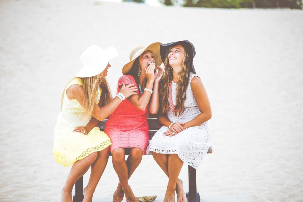 women laughing sitting on a bench in hats and dresses